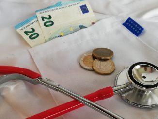 geld op een wit uniform van verpleegkundige met stethoscoop